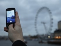A Google employee holds up a mobile phone to demonstrate how the new Goggles application recognises the London Eye as seen from Westminster Bridge in central London