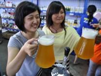 Chinesen lieben deutsches Bier. Hier feiern zwei Frauen beim Deutschen Bier-Festival in Qingdao.