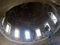 A Palestinian worker cleans windows of vandalised mosque in Yasuf