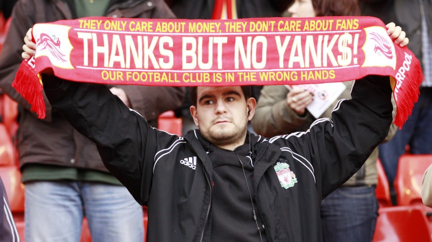 A Liverpool fan holds up a scarf in protest after their English Premier League soccer match against Blackpool in Liverpool