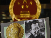 A protester holds up a sign featuring a portrait of Liu Xiaobo and a Nobel Prize medal during a demonstration outside the China liaison office in Hong Kong