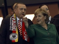 Turkish Prime Minister Erdogan and German Chancellor Merkel await the start of the Euro 2012 qualifying soccer match between Turkey and Germany at the Olympic stadium in Berlin