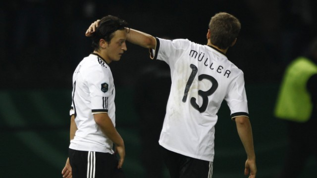 Germany's Thomas Mueller (R) congratulates team mate Mesut Oezil after he scored a goal against Turkey during their Euro 2012 qualifying soccer match at the Olympic stadium in Berlin