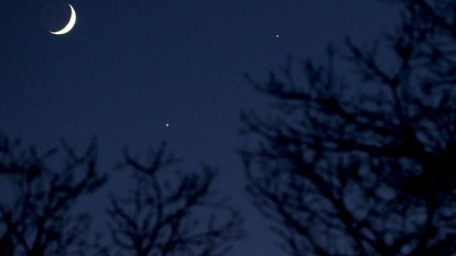 Mondsichel nahe der hellsten Planeten am Sternenhimmel Venus und Jupiter