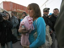 Elizabeth Segovia, wife of freed miner Ariel Ticona, walks past journalists to enter the Copiapo Hospital with her baby daughter