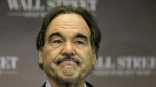 US Director Oliver Stone poses during a photocall promoting his film Wall Street: Money Never Sleeps in Berlin