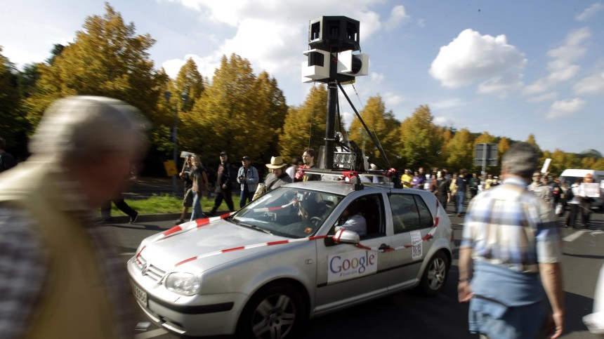 Demonstrators drive a car decorated to represent the Google Car used to create street view maps during a demonstration for data privacy in Berlin