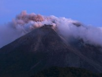 Mount Merapi emits smoke as it is seen from Kali Tengah village near Yogyakarta