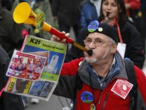 Demonstrator blows a trumpet during a protest in Stuttgart