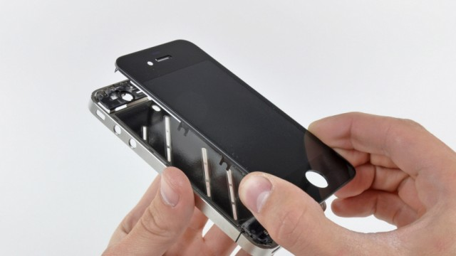 The front panel is removed from the iPhone 4 during iFixit's teardown of the phone in San Luis Obispo