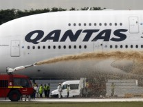 Qantas Airways 380 passenger plane flight QF32 is sprayed by rescue services after making an emergency landing at Changi airport in Singapore