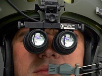 A French pilot tests a new European night vision binoculars on board a Swedish helicopter at the Paris Air Show at le Bourget