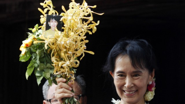 Aung San Suu Kyi holds a bunch of flowers before addressing supporters outside the headquarters of her National League for Democracy party in Yangon
