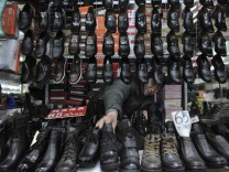 A vendor arranges leather shoes at a market in Shenyang