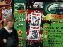 A woman walks past newspaper headlines posted on a news stand on O'Connell street, Dublin