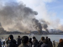 People look as smoke rises from South Korean Yeonpyeong Island after being hit by dozens of artillery shells fired by North Korea