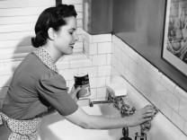 Frau putzt Waschbecken/Geschirr 1950