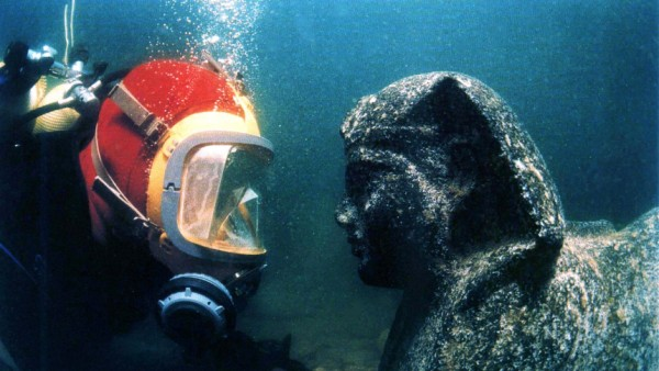 FRENCH ARCHAEOLOGICAL DIVER INSPECTS A STATUE