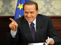 Italy's Prime Minister Berlusconi gestures during a news conference in Naples