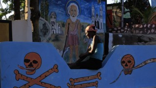 Haitian woman waits for the start of a voodoo ceremony inside a voodoo temple during Day of the Dead celebrations in Belladere
