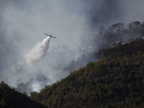 A firefighting aircraft flies over a forest fire on Mount Carmel near the northern city of Haifa