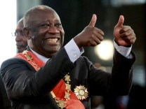 Ivory Coast's President Laurent Gbagbo flashes two thumbs-up during his inauguration at the presidential palace in Abidjan