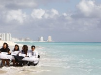 Activists from the 350.org sit on a table partially submerged in water as they pretend to represent countries taking part in the U.N. climate talks during a staged news conference at a beach in Cancun