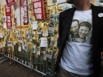 Protester in Liu Xiaobo t-shirt stands outside Chinese liaison office during protest in Hong Kong