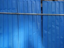 A worker peers through a gap in a barrier he is erecting outside the entrance of the residential compound where Liu Xia lives in Beijing