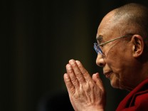 Dalai Lama greets journalists as he arrives for a news conference at the Mind and Life conference in Zurich