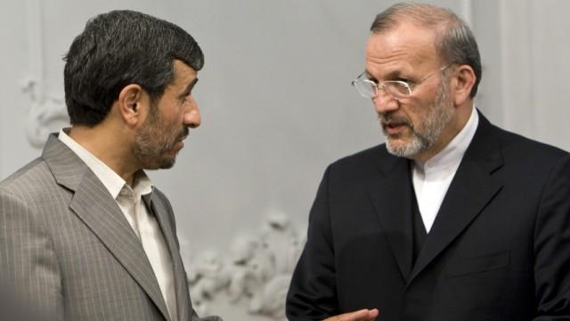 File photo of Iran's President Ahmadinejad speaking to Foreign Minister Mottaki in Tehran