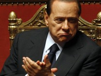 Italian Prime Minister Silvio Berlusconi claps during a session at the Senate in Rome
