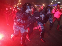 Russian riot police officers detain a man during a rally in Mosco