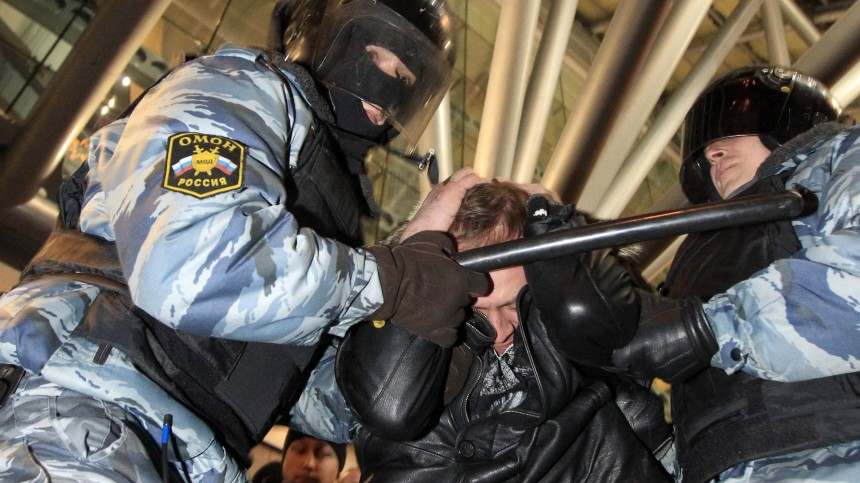 Police officers detain a man during an operation to prevent outbreaks of ethnic violence near a train station in Moscow