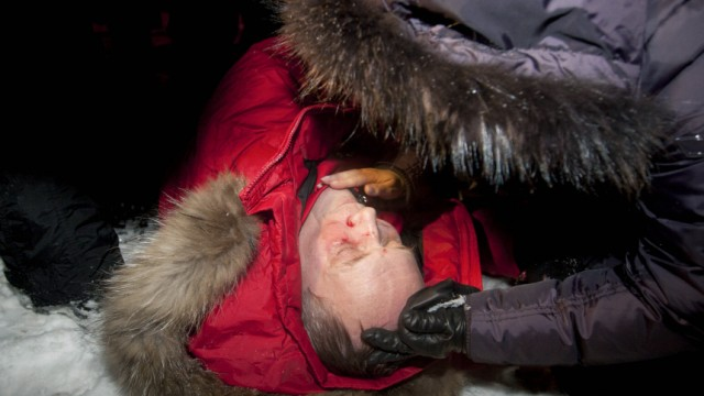 Presidential candidate Vladimir Neklyayev lies on a street after he was beaten during a rally in Minsk
