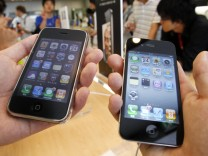 A customer holds a new iPhone 4 and an earlier version of the iPhone in Apple Inc's store in the Ginza district of Tokyo
