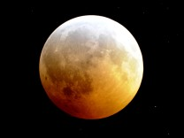 The Moon is engulfed in the Earth's shadow as it nears the peak of a rare winter solstice total lunar eclipse as viewed through a telescope from Palm Beach Gardens