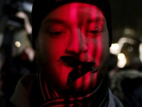 A protester wears tape over his mouth during a demonstration against a new media law in downtown Budapest