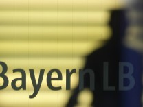 File photo of an employee of the Bavarian public sector bank BayernLB walking near the bank's logo in Munich