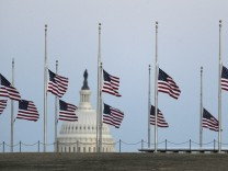 The US Capitol dome is shown in the background as flags fly at half staff in Washington