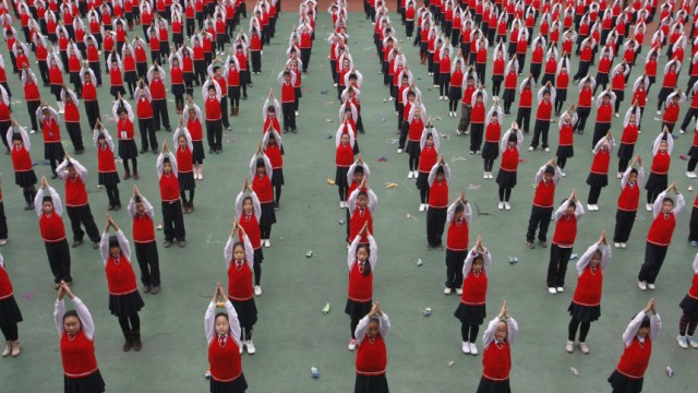 Pupils attend a Yoga exercise session during break time at a primary school in Suining