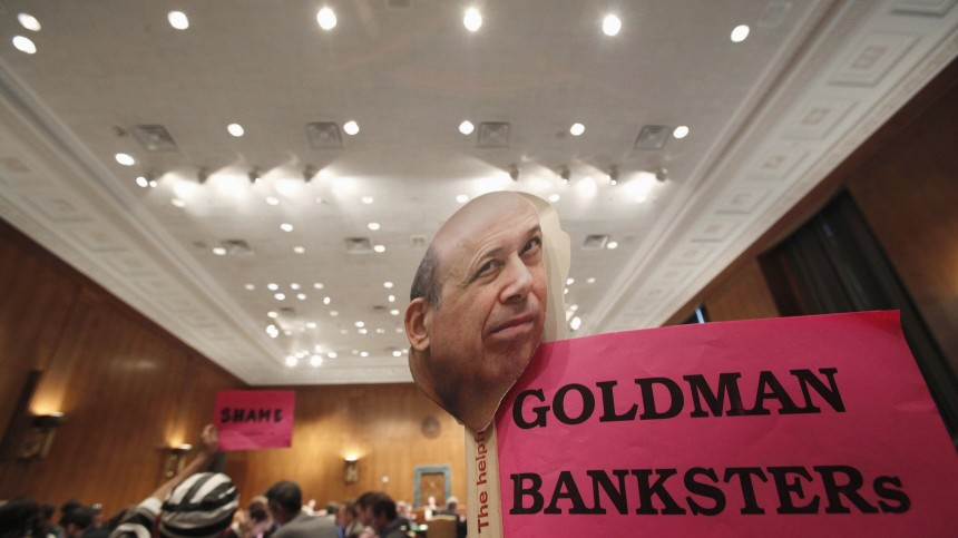A protestor holds a sign with a picture of Goldman Sachs's Blankfein during the testimony at a Senate Homeland Security and Governmental Affairs Investigations Subcommittee hearing on Capitol Hill in Washington