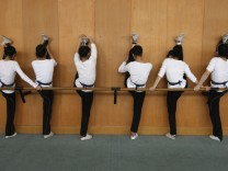 Students stretch against a wall during physical practice for Yueju opera at an art school in Hangzhou