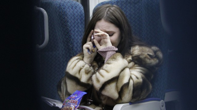 A woman cries, while talking on the phone to an acquaintance who is at Domodedovo airport, as she travels by train to the airport from Moscow