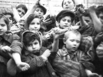 File photograph of  children, who survived Auschwitz II-Birkenau, show their tattooed identification numbers