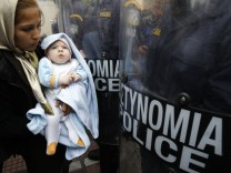 An Afghan asylum seeker holding a child stands in front of riot policemen during a demonstration in Athens