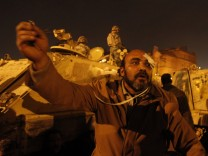 A protester gestures as others gather around army vehicles at Tahrir Square in Cairo