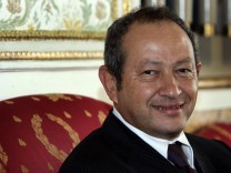 Egyptian businessman Sawiris smiles before news conference in Rome