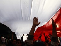 Opposition supporters carry a huge Egyptian flag amid the crowd in Tahrir Square