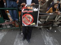 Protester holds poster with defaced picture of Egypt's President Mubarak in front of the Egyptian Parliament building in Cairo